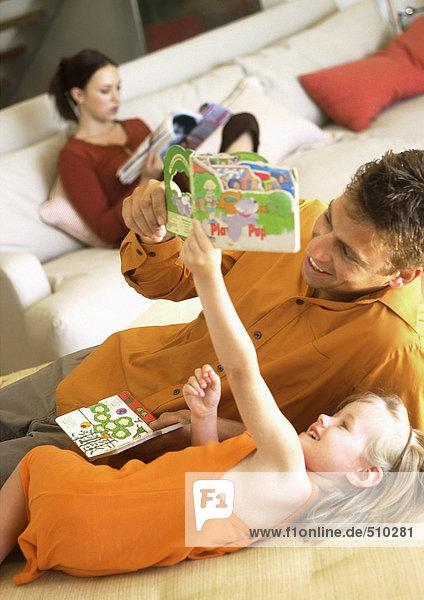 Vater und Tochter schauen auf das Buch  lächelnd  Frau sitzt auf dem Sofa im Hintergrund