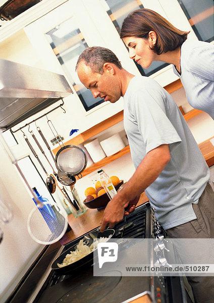 Paar in der Küche  Mann kocht  während Frau über die Schulter schaut  Seitenansicht