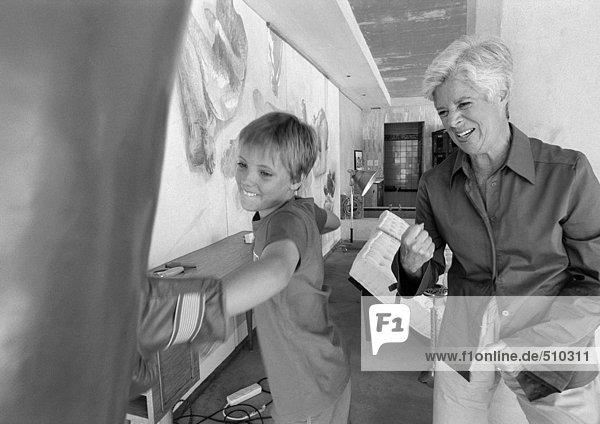 Kind schlägt Boxsack  Seniorin feuert ihn an  s/w