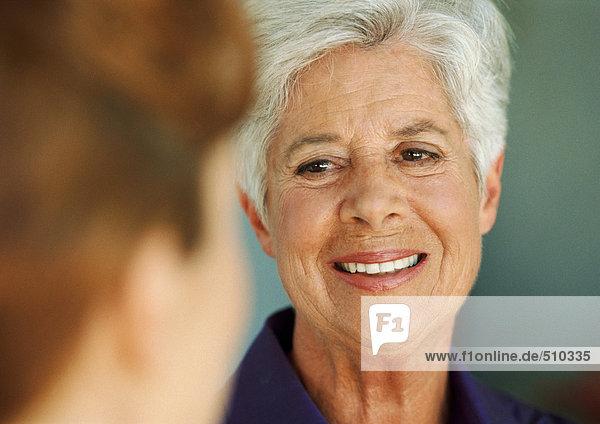 Ältere Frau sieht jüngere Frau  Nahaufnahme  verschwommener Vordergrund