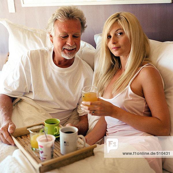 Paar im Bett sitzend  Mann mit Getränkeschale