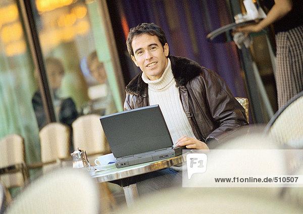 Mann mit Laptop-Computer auf der Café-Terrasse