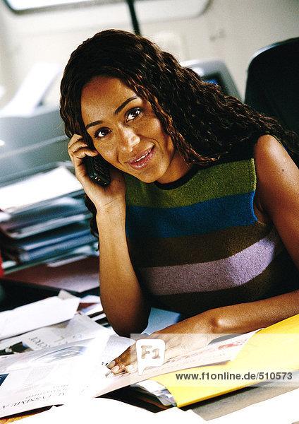 Frau am Schreibtisch mit Handy  Portrait