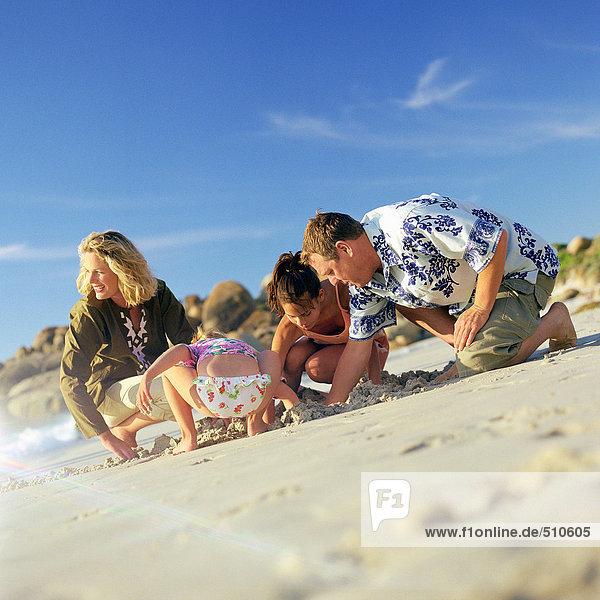 Pärchen und Kinder beim Graben im Sand