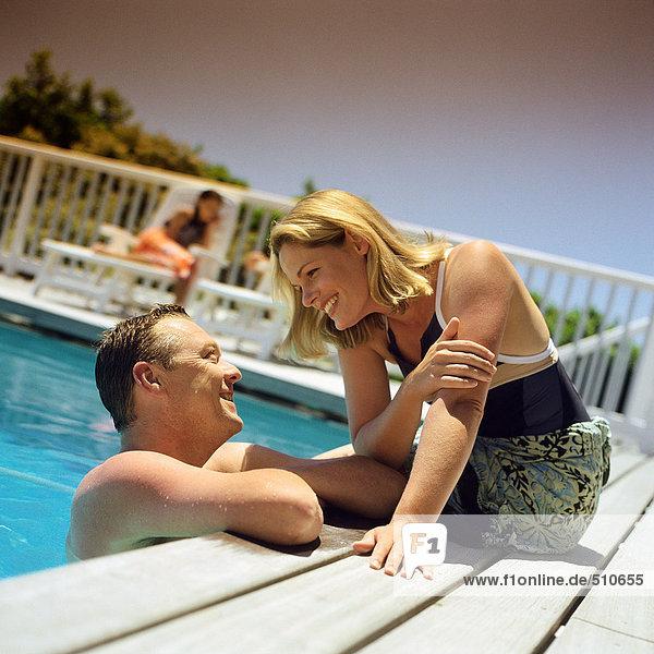 Liebespaar im Resort  Mann im Gespräch mit Frau am Beckenrand