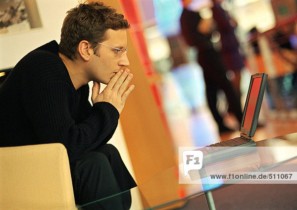 Man using laptop  hands in front of mouth  side view