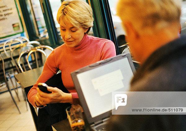Erwachsenes Paar im Restaurant  Mann mit Laptop  Frau mit Handy.