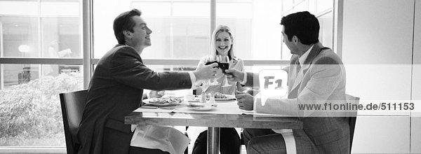 Zwei Geschäftsleute sitzen am Tisch und klirren an den Gläsern  s/w  Panoramablick