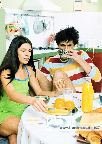 Young couple sitting at table having breakfast.