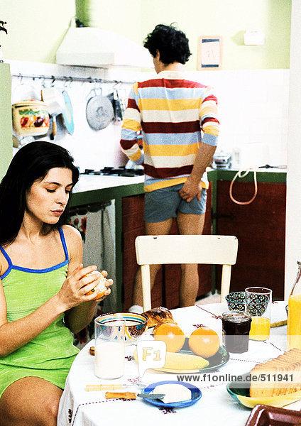 Frau am Frühstückstisch sitzend  Mann stehend  hinten kratzend