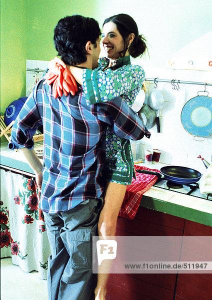 Mann und Frau umarmen sich in der Küche.