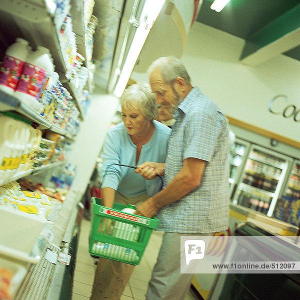 Älteres Paar im Supermarkt  Mann hält Korb