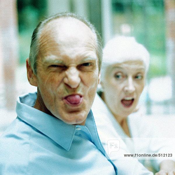 Reifer Mann mit herausgestreckter Zunge  Frau im Hintergrund