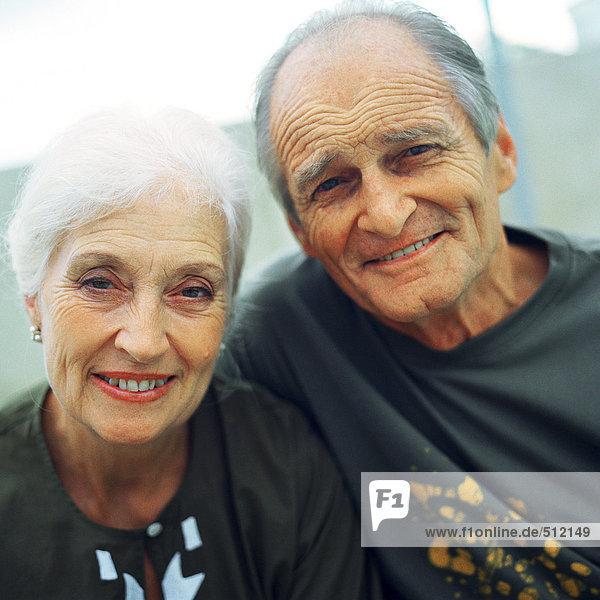 Ein reifes Paar eng beieinander  lächelnd vor der Kamera.