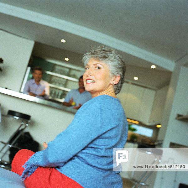 Reife Frau sitzend  über die Schulter schauend  Männer stehend in der Küche im Hintergrund
