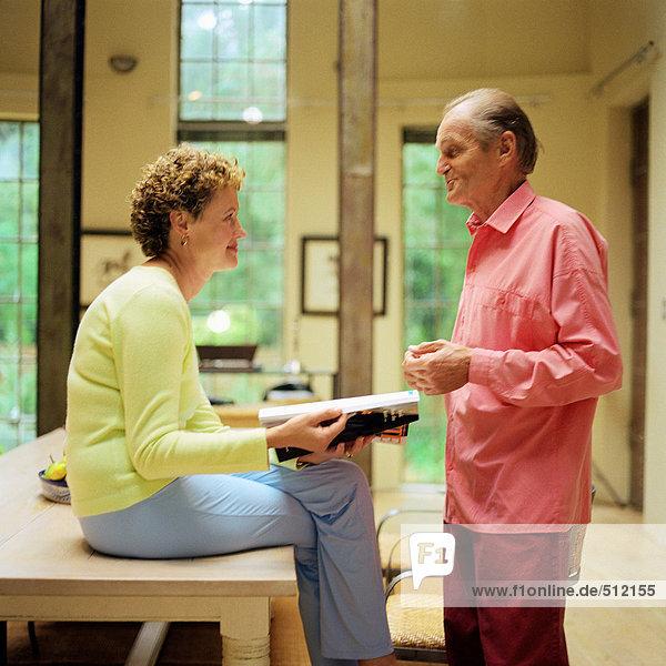 Erwachsenes Paar von Angesicht zu Angesicht  Frau auf dem Tisch sitzend  Mann stehend  Seitenansicht