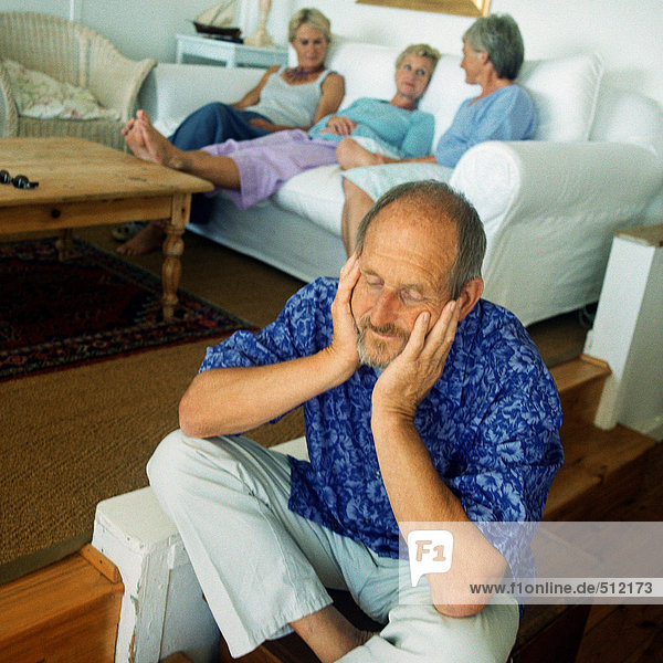 Mature man sitting on floor  three women in background on couch