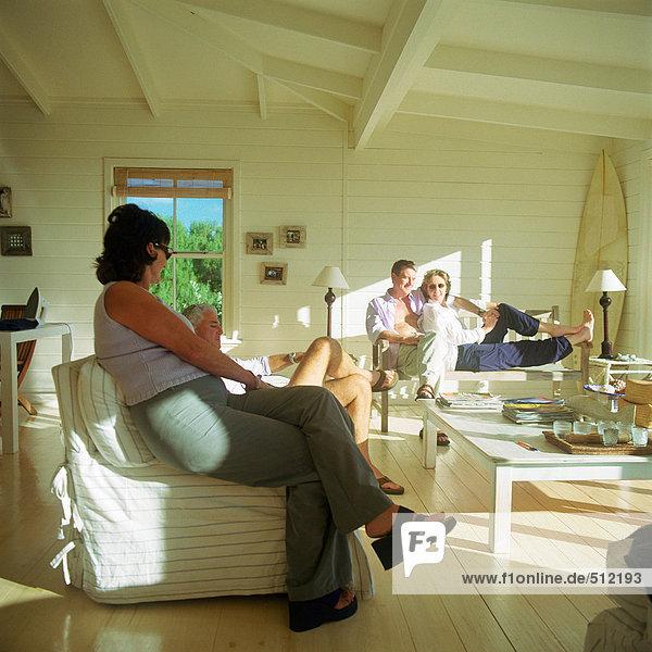 Vier Personen sitzen auf Sofas
