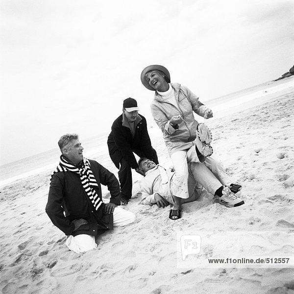 Reife Gruppe spielt am Strand  s/w.