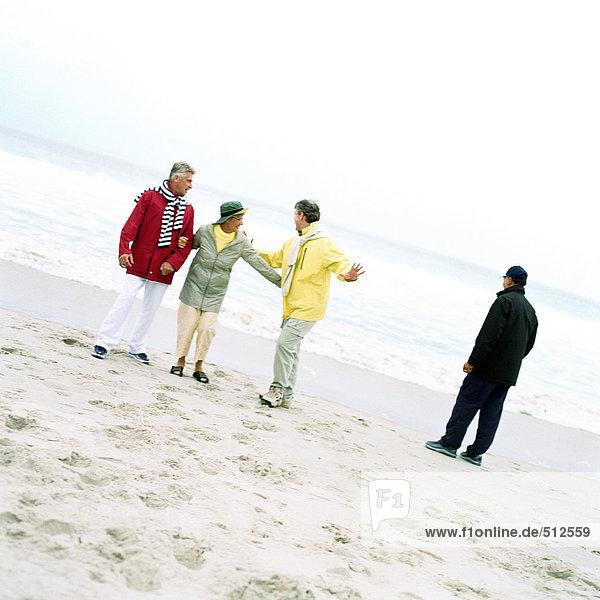 Reife Gruppe am Strand am Meer.