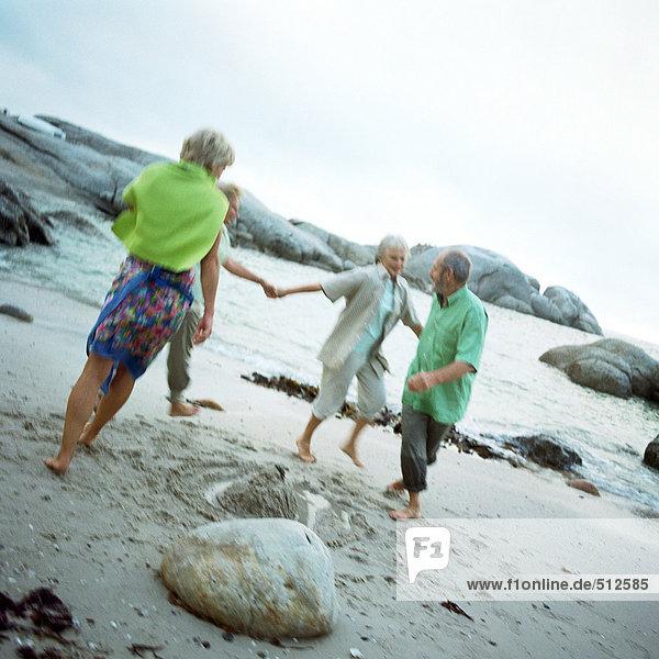Reife Gruppe  die am Strand spielt.