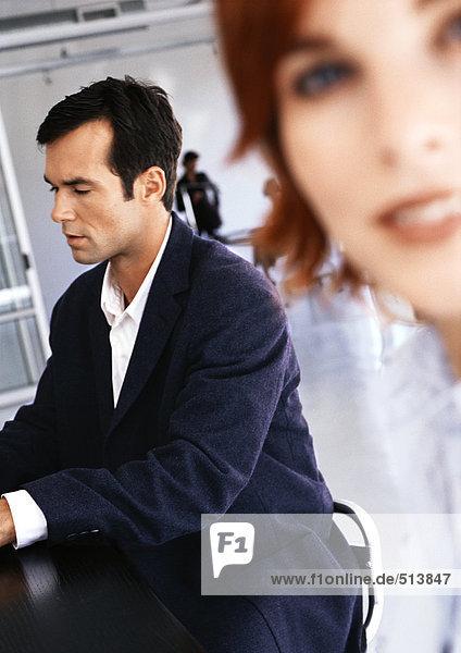 Geschäftsmann am Schreibtisch sitzend  Frau lächelnd