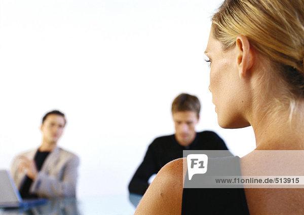 Frau sitzt gegenüber zwei Männern im Büro  Rückansicht