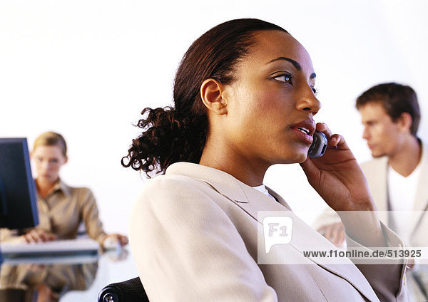 Businesspeople in office  woman using cell phone  side view