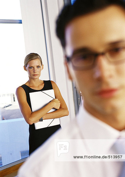 Geschäftsfrau hält Mappe hinter Geschäftsmann