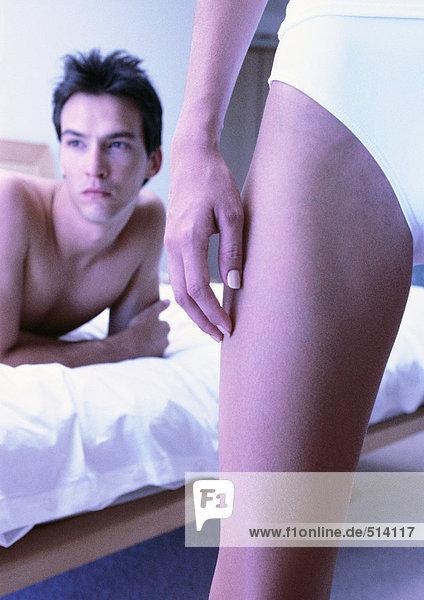 Mann auf dem Bett liegend  Frauenbein im Vordergrund