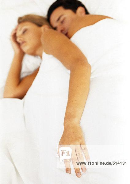 Paar schläft im Bett  Fokus auf die Hand der Frau im Vordergrund