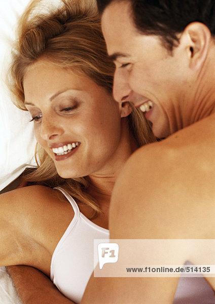 Paar umarmend im Bett  Kopf und Schultern  lächelnd  Nahaufnahme  Portrait