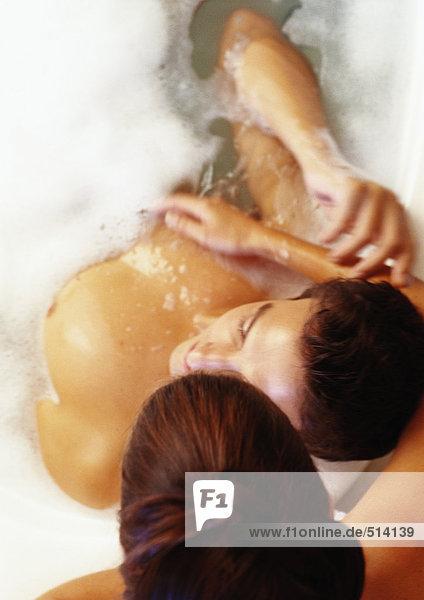 Frau lehnt sich über den Mann im Bad  erhöhte Aussicht