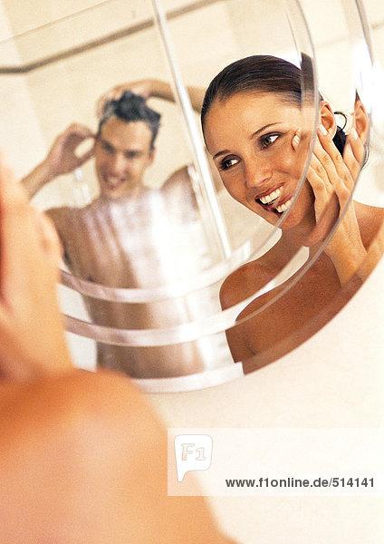 Ein Paar schaut sich im Spiegel im Badezimmer an.