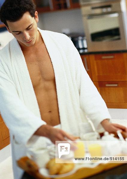 Mann im Bademantel bei der Zubereitung des Frühstückstabletts
