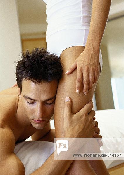 Mann auf Bett lehnt Kopf gegen die Beine der Frau