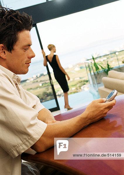 Mann mit Handy  Frau auf der Terrasse im Hintergrund