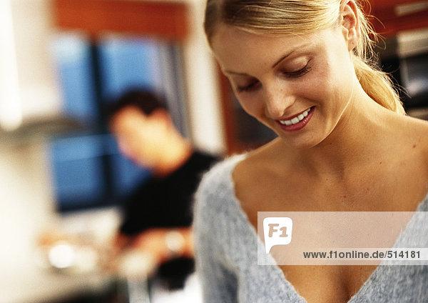 In der Küche  Frau lächelnd und herabblickend  Mann im Hintergrund