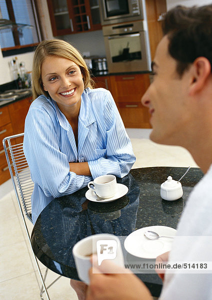 Mann und Frau am Tisch mit Tassen und Untertassen  Rückansicht des Mannes  verschwommen  Fokus auf lächelnde Frau im Hintergrund