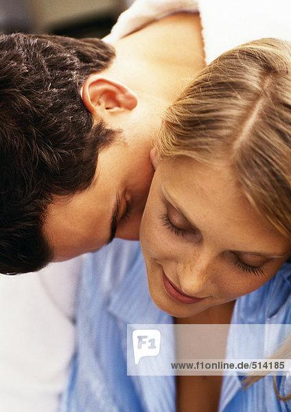 Mann lehnt sich über die Schulter der Frau  küsst den Hals der Frau  Nahaufnahme