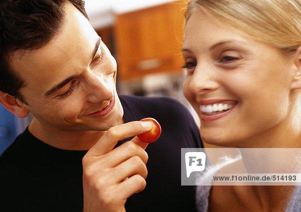 Mann füttert Frau Kirschtomate mit Fingern  Kopf und Schultern  Nahaufnahme  verschwommene Bewegung