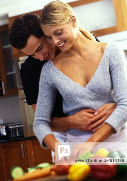 Frau am Tresen stehend mit Gemüse bedeckt  Mann hinter der Frau mit Armen um die Hüfte