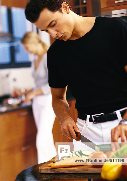 Mann schneidet Gemüse in der Küche  Mittelteil