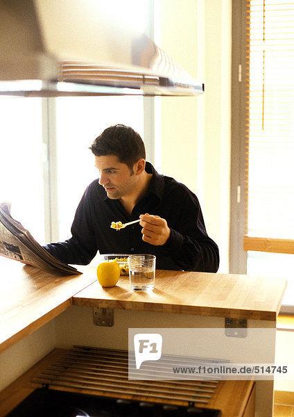 Mann isst und liest Zeitung