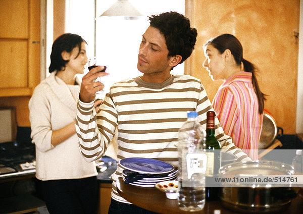 Man holding wine glass in kitchen  two women talking in background