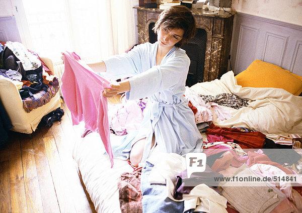 Frau kniend auf dem Bett zwischen Kleidern  hochhaltend und mit Blick auf Pullover