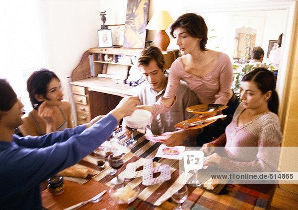 Vier Personen sitzen am Tisch  Frau nimmt ihr Geschirr und Besteck mit.