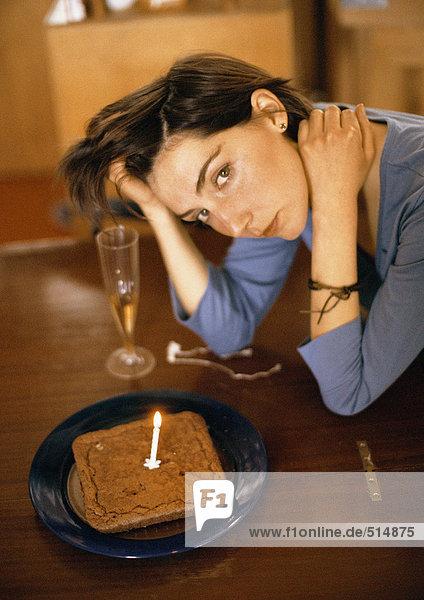 Frau allein am Tisch mit Kuchen und einer Kerze  Portrait