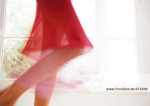 Frau geht vor dem Fenster  unterer Teil  verschwommene Bewegung.
