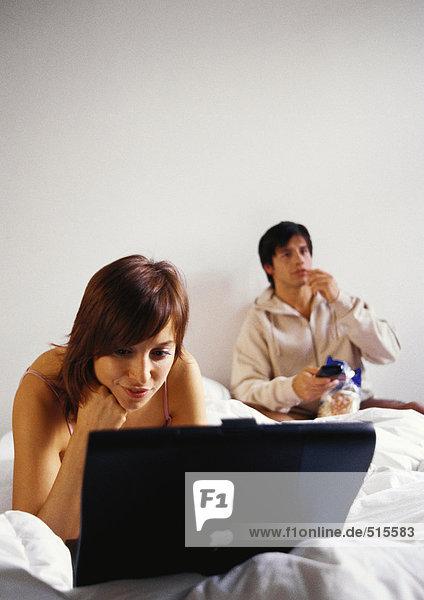 Frau arbeitet am Laptop im Bett  Mann isst.